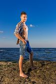 picture of nearly nude  - Attractive Young Fashion Sexy Man On Rock Near The Sea Water - JPG