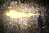 picture of fire-breathing  - Angry businessman spitting fire flame from mouth illuminated the dark mottled concrete wall background - JPG