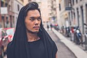 stock photo of tunic  - Young handsome Asian model dressed in black tunic posing in the city streets - JPG
