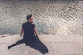 pic of tunic  - Young handsome Asian model dressed in black tunic sitting by an artificial basin - JPG