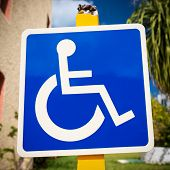 image of handicap  - Blue handicapped sign with wheelchair at tropical street - JPG