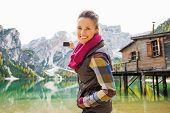 picture of pier a lake  - A smiling brunette in outdoor gear is aiming her digital camera out at Lake Bries and the Italian Dolomites in the background - JPG