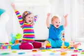 foto of happy day  - Kids playing with wooden toys. Two children cute toddler girl and funny baby boy playing with wooden toy blocks building towers at home or day care. Educational child toys for preschool and kindergarten. ** Note: Soft Focus at 100%, best at smaller sizes - JPG
