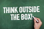 stock photo of thinking outside box  - Hand writing think outside the box on chalkboard - JPG