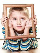stock photo of sad boy  - Portrait of little sad blonde boy child holding photo frame framing his face looking up studio shot isolated on white - JPG