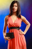 image of evening gown  - Fashion elegant evening outfit. Stylish woman fashionable mixed race girl orange party gown holding black leather handbag bag night club