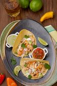 image of tacos  - Two shrimp tacos with salsa guacamole beer garnished with mini bell pepper and lime - JPG