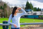 stock photo of biracial  - Young biracial teen girl standing leaning against railing at park shading eyes to look off to side - JPG