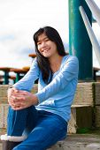 picture of biracial  - Young biracial teen girl in blue shirt and jeans sitting on wooden steps outdoors on overcast cloudy day - JPG