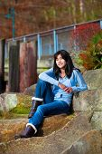 pic of biracial  - Young biracial teen girl in blue shirt and jeans sitting on large boulder smiling and reclining - JPG