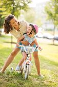 picture of laugh  - A mother hugs her daughter from behind as the daughter wearing a pink helmet looks up towards her mother laughing and proud - JPG