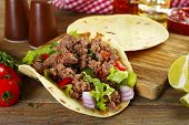 stock photo of tacos  - Mexican food Taco on wooden cutting board - JPG