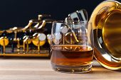 stock photo of saxophones  - Saxophone and whiskey on a wooden table - JPG