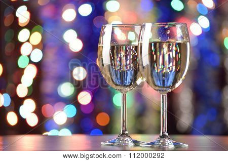 Glasses Of Sparkling Wine On The Background Of Colorful Bokeh