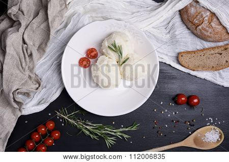 Side dish of mashed potatoes with cherry tomatoes, rosemary and fresh bread. High angle view.