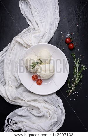 Mashed potatoes on plate with cherry tomatoes and rosemary. Side dishes, high angle view.