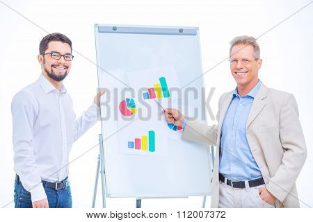 Cheerful businessmen working with charts.