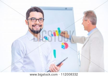 Two businessmen presenting chart materials.