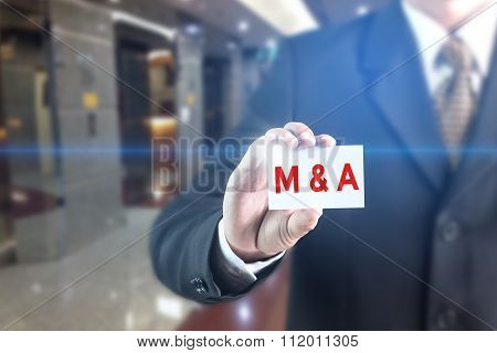 A Businessman holding a white sign with the message M&A (Merger and Acquisition).