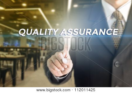 Business man pressing hand quality assurance word on virtual screen