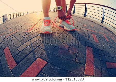 young woman runner tying shoelace on seaside