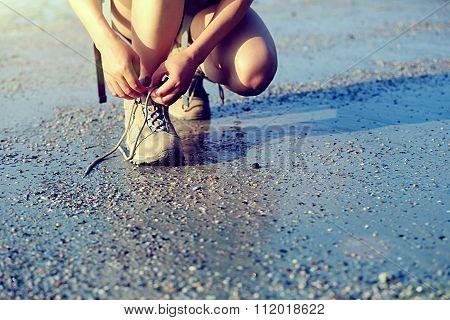 woman hiker tying shoelace on sunrise beach