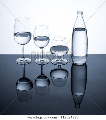 Glassware And Bottle Filled With Water On White Background