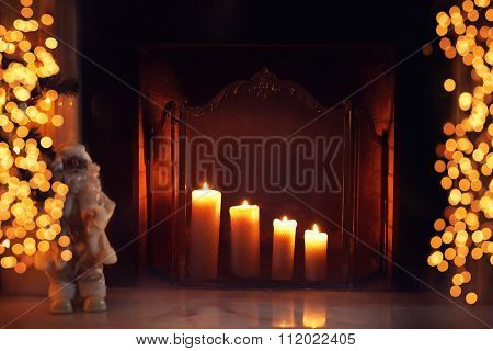 Christmas Fireplace With Burning Candles And Lights Bokeh In Home Interior