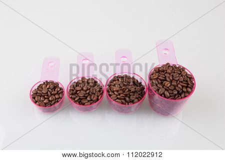 Coffee Beans In Measuring Cups Of Various Sizes On White