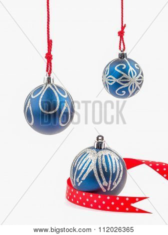 Three Hanging Christmas Baubles Isolated On White
