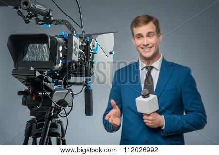 Smiling newsman with a microphone.