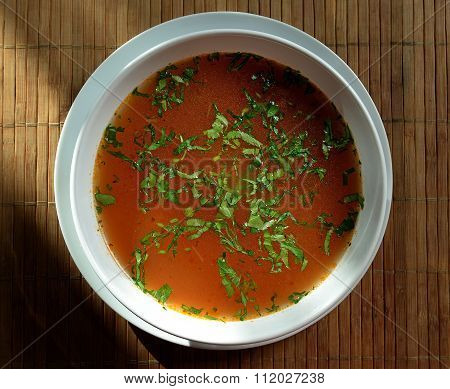 Broth, bouillon, clear soup in a large white bowl close-up