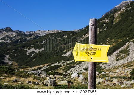 Signpost to Okoto lake near Bansko, Bulgaria and mountain background