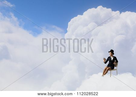 Pretty girl wearing retro hat siting on chair with alarm clock in hand