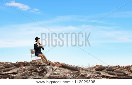 Pretty girl wearing retro hat siting on chair with cup in hand