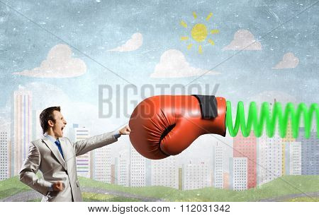 Young determined businessman fighting boxing glove on spring