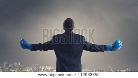 Businessman winner standing with back in suit and boxing gloves