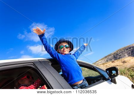 happy little boy and girl travel by car in mountains
