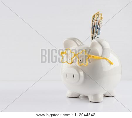 Piggy Bank With Yellow Glasses And Three 50 Dollar Bills