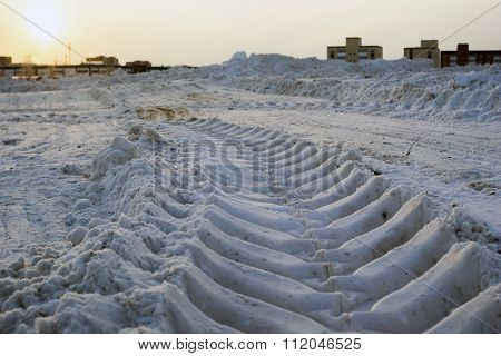 Deep imprint of a tractor in the snow.