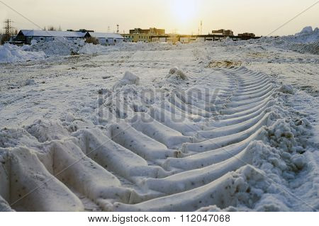 Imprint  tractor in snow on cleared site for construction.