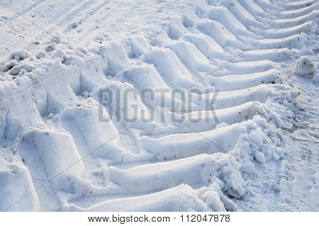 The imprint of the wheels in snow.