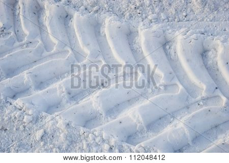 The imprint of  wheels   big tractor in  snow.