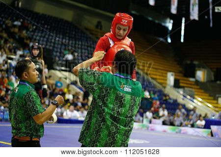 JAKARTA, INDONESIA - NOVEMBER 18, 2015: Maryam Hashemiforoud of Iran (red) gets her gloves refitted during the women's 70kg Sanda finals at the 13th World Wushu Championship 2015 in Istora Senayan.