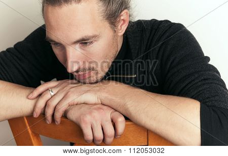 Sad Young Asian Man Sitting On Wooden Chair