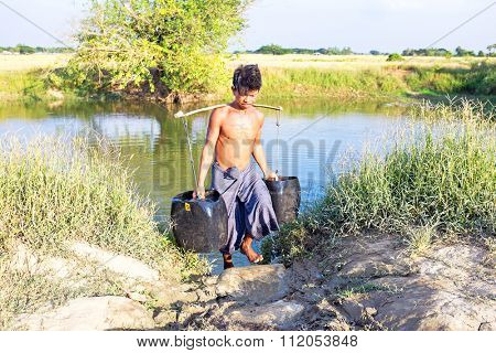 YANGON, MYANMAR - November 25, 2015: Water carrier with two buckets getting water in the countryside from Myanmar