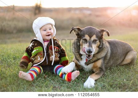Happy Baby Bundled Up Outside In Winter With Pet Dog