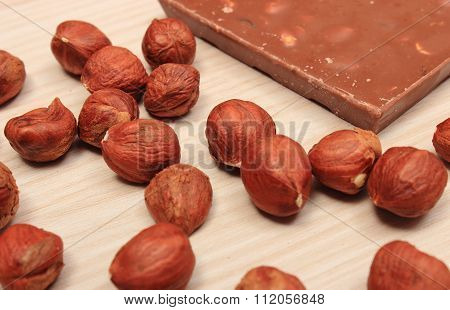 Nutritious Chocolate And Hazelnuts On Wooden Table