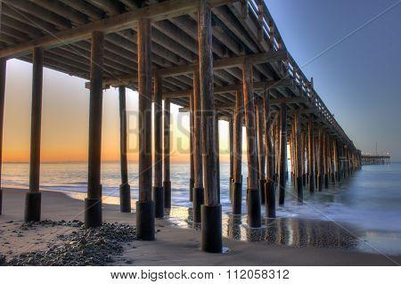Glow of dawn under wooden pier