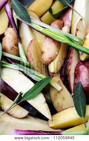 Raw potatoes sliced in wedges with fresh sage herb and spring onion, ready for home cooking, roasting or baking